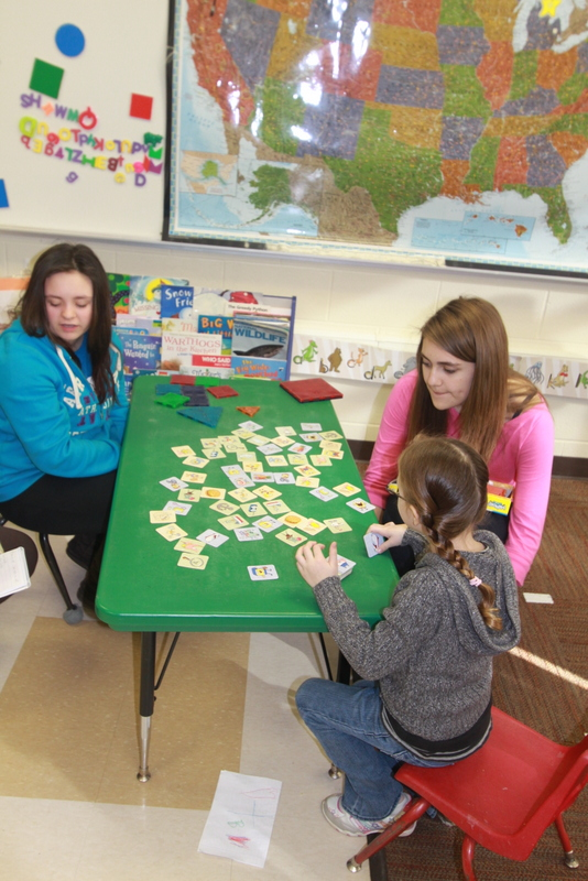 """Zoe O'Neill and Victoria Zavasky play Memory with a student in the GSRP classroom.  Zoe says her favorite part of working with the early childhood students is, """"…playing with kids and watching them be happy.""""  Victoria says her favorite part is, """"…watching the little kids play."""""""