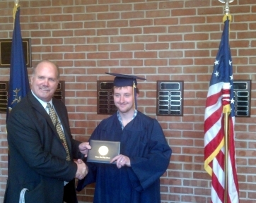Scott Perkett receives his high school diploma from West Principal Tim Zeeman and becomes the first Lapeer Virtual Learning Center student to earn his diploma.