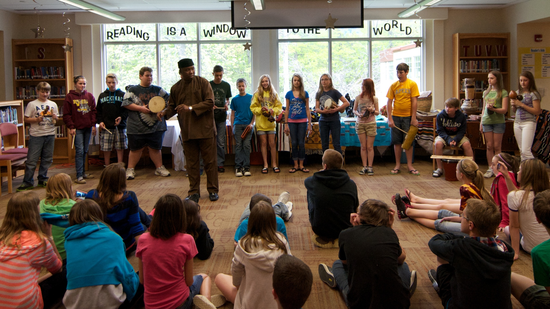 Dr. Stephen Uche, of Ann Arbor, talks to Rolland-Warner students about various instruments endemic to Africa, many actually constructed by students of elementary-school-age.