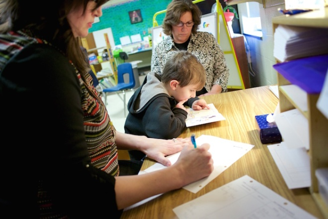 Amber Weidinger, left, and Joanne LeBlanc, center, take notes as six-year-old Caleb Rutkowski starts his 30-minute Reading Recovery session at Lynch Elementary.