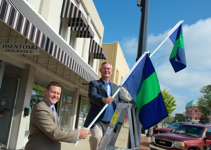 LCS Superintendent Matt Wandrie and Lapeer DBA President Dan Osentoski show off the new Spirit Flags in downtown Lapeer.